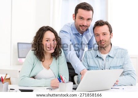 View of Two interns working together assisted by their course supervisor - stock photo
