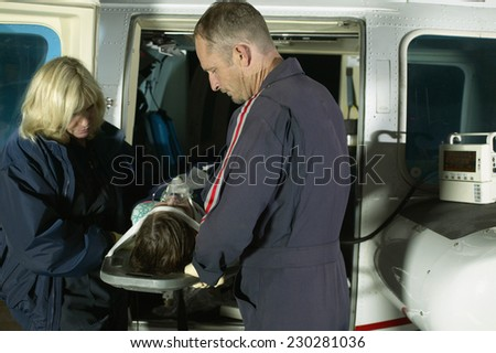 View of two paramedics examining a victim on a gurney - stock photo