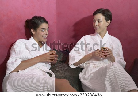 View of two young women drinking as they relax in bathrobes - stock photo