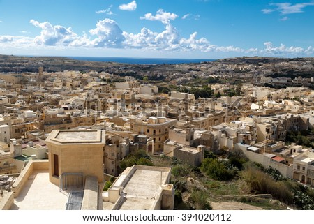 View of Victoria city in Malta, with historical limestone buildings, on cloudy blue sky background.