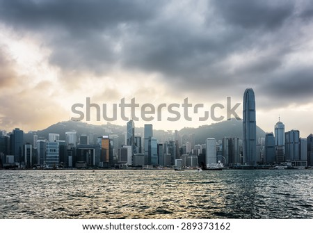 View of Victoria harbor and skyscrapers in business center of Hong Kong Island with stormy sky. Hong Kong is popular tourist destination of Asia and leading financial centre of the world.