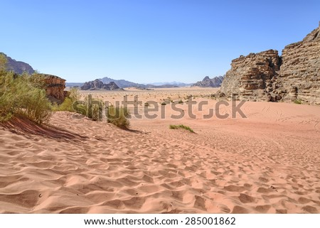View of Wadi Rum desert in Jordan. Wadi Rum is a valley cut into the sandstone and granite rock in southern Jordan 60 km (37 mi) to the east of Aqaba; it is the largest wadi in Jordan. - stock photo