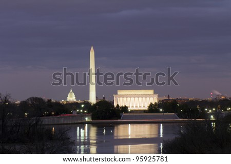 View of Washington DC with Capitol, Washington Monument and Lincoln Memorial, reflection on potomac river, at sunset - stock photo