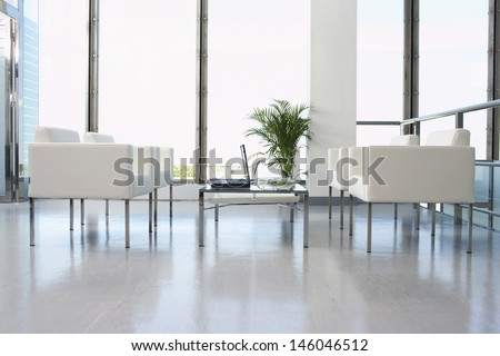 View of white armchairs and laptop in spacious and modern waiting room at office - stock photo