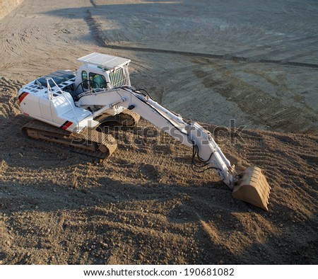 View of white excavator on the construction site - stock photo
