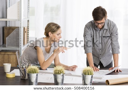 View of woman and man working in modern office with some papers