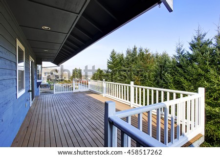 View of wooden walkout deck with white railings and nice view. Northwest, USA