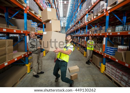 View of worker bringing down some cardboard boxes in a warehouse