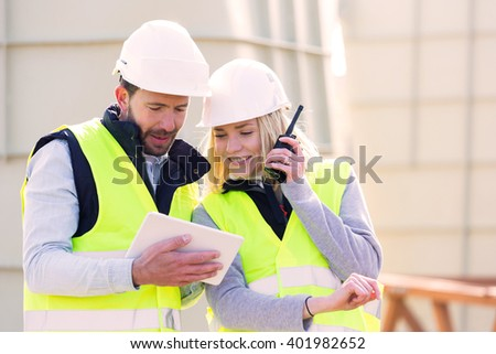 View of Workers on a construction studying blueprints - stock photo