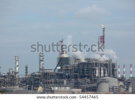 View of working oil refinery plant with  curling air emission smoke. - stock photo