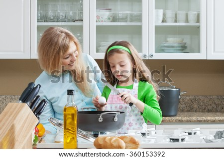 view of young beautiful girl cooking at the kitchen with her mama - stock photo