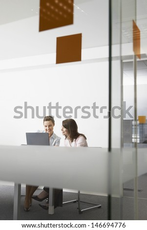 View of young businesswomen discussing over laptop through glass wall in office - stock photo