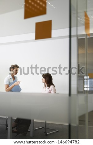 View of young businesswomen discussing through glass wall in office - stock photo