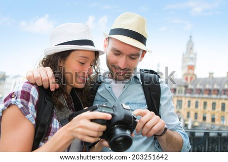 View of Young couple of tourist watching photographs
