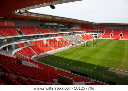 View on an empty football (soccer) stadium with red seats.