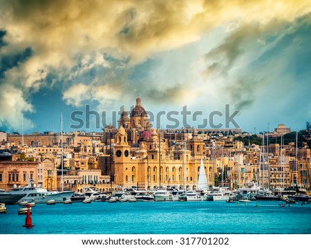 view on Birgu coast from the sea in Malta at sunset - stock photo