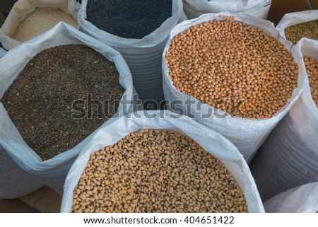 View on different assorted raw legumes in white bags from above. Chick peas, beans, lentils - stock photo