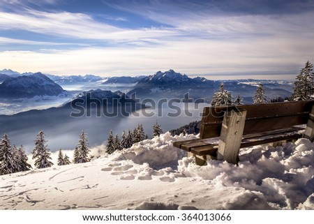 View on distant snow covered swiss mountains and lake from bench in the winter - stock photo