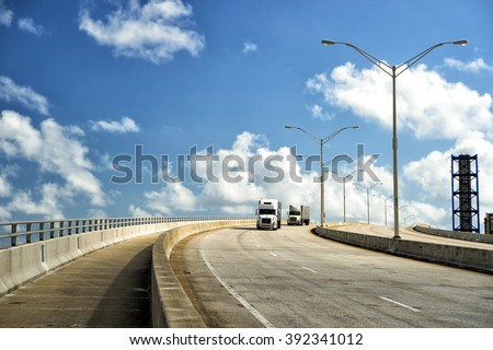 View on highway road with two transit lorry street lamps outdoor sunny weather on cloudy blue sky background, horizontal picture - stock photo