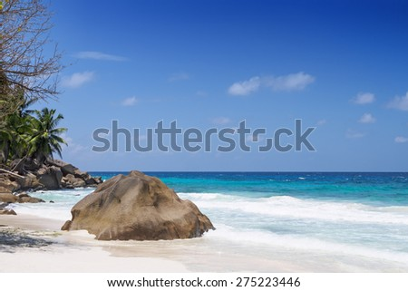 View on idyllic tropical beach with rocks and waves, clear blue sky, turquoise ocean, Seychelles islands - stock photo