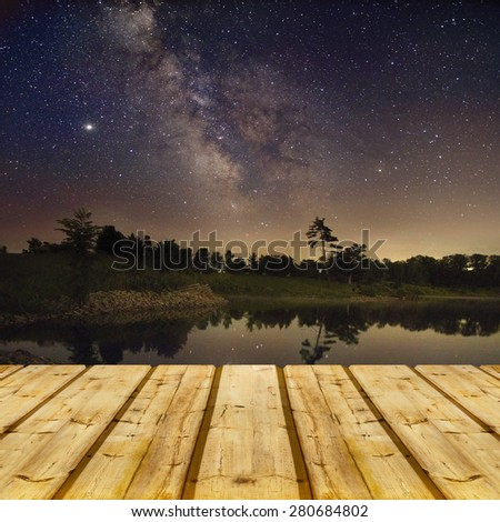 view on lake near the forest with some pine treesat night on mountain background in moon light - stock photo
