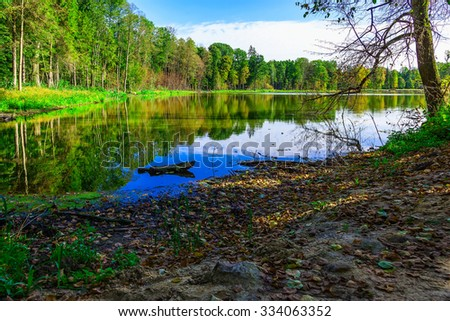 View on Lake Surrounded by Colorful Trees in Autumn Season - stock photo