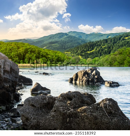 view on lake with rocky shore and some boulders near forest on mountain  with high vista far away - stock photo