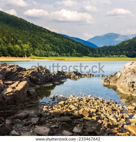 view on lake with rocky shore and some boulders near pine forest on mountain  with high vista far away - stock photo