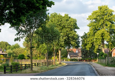 View on long road in village with houses fence and lush green trees outdoor sunny day on natural background, horizontal picture - stock photo