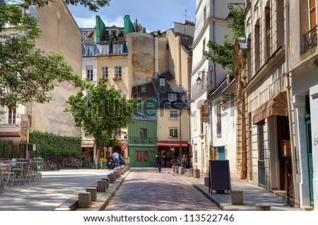 View on narrow cobbled street among traditional parisian buildings in Paris, France. - stock photo