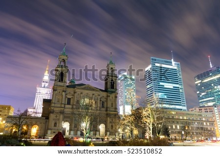 view on old church and modern skyscrapers in Warsaw at night, Poland