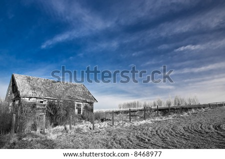 View on old house in b&w under blue sky. Infrared.