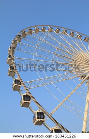 View on part of ferris Wheel attractions in city park against sky