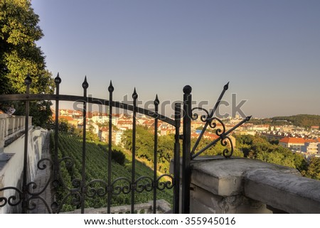 View on Prague cityscape, Vinohrady and Nusle area, from the popular Havlicek park (Havlickovy sady aka Grebovka) during a nice summer sunny day behind a decorative metallic fence/gate - stock photo