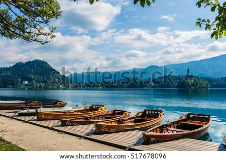 View on several polished row boats on Lake Bled, Slovenia. Julian Alps. Anchored boats by the pier. Some wooden boats in a row. Mountains and famous church on small island on background. Sunny day.