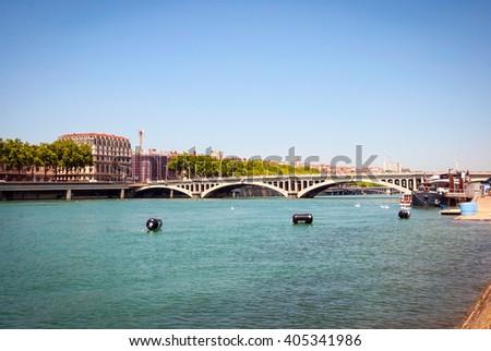 View on sunlit bridge over calm river in Lyon, France - stock photo