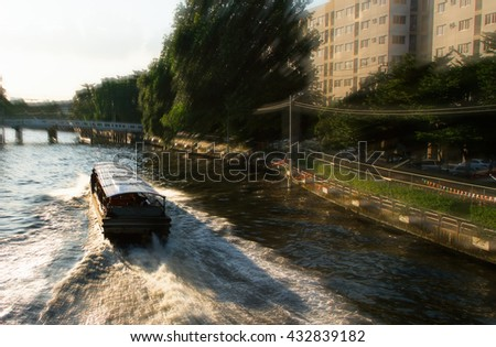 View on the bridge through the river channel with boat, typical picture of canals in Bangkok. - stock photo