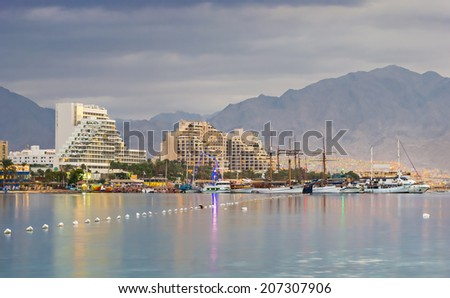 View on the central beach of Eilat at dawn. Eilat is a famous city with beautiful beaches and resort hotels packed with thousands of vacationers and relaxing tourists from around the world - stock photo