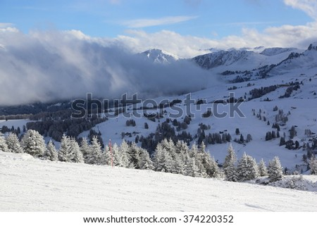 View on the Langkofel and Plattkofel (Sassolungo and Sassopiatto) dolomites mountains over the Alpe di Siusi or Seiser Alm in South Tyrol, Italy in winter.