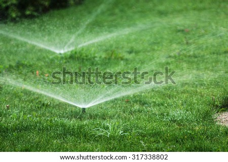 View on the two sprinklers throwing out water drops over green grass field - stock photo