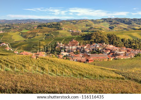 View on town of Barolo among colorful hills and vineyards of Piedmont at fall in Northern Italy.