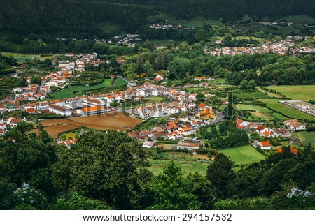 View on town of Furnas, located in the same name a civil parish in the municipality of Povoacao on the island of Sao Miguel in the Portuguese Azores, as seen from the Pico do Gaspar Belvedere. - stock photo