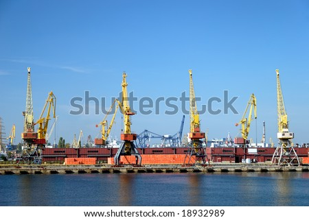 View on trading port with cranes, containers and cargoes - stock photo