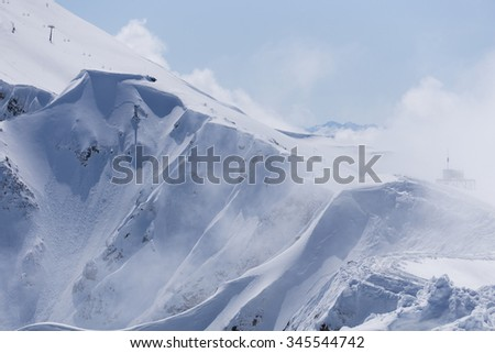 View on winter snowy mountains and blue sky above clouds, Krasnaya Polyana, Sochi, Russia - stock photo