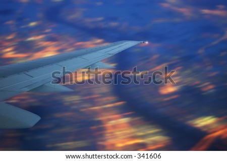 view out of an airplane passing over a big illuminated city at night - stock photo
