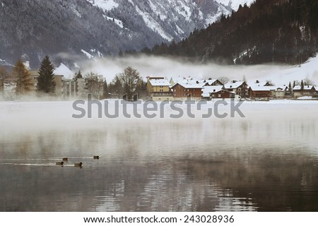 View over a Swiss Village by a lake in the Alps, covered in snow during winter. - stock photo