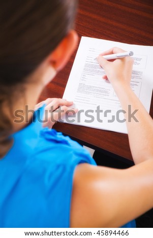 View over a woman's shoulder while signing a contract. - stock photo