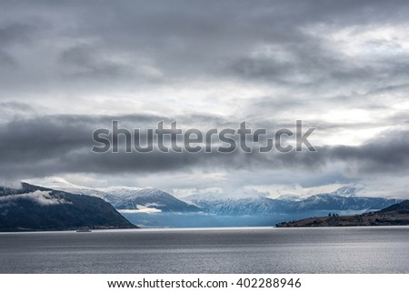 View over Norwegian fjord with heavy rain clouds rolling in in the sky - stock photo