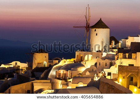 View over Oia at dusk, with beautiful windmill, Santorini island, Greece - stock photo
