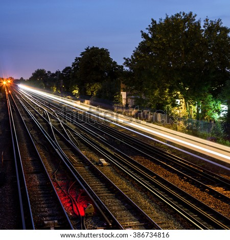 View over railway lines at mid-twilight with the light streak of a train that has recently passed. South London, UK.  Square version. - stock photo